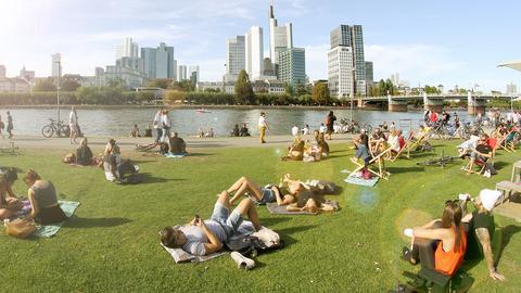 Am Frankfurter Mainufer sitzen Menschen in der Sonne und freuen sich über das schöne Wetter. Im Hintergrund die Frankfurter Innenstadt mit ihren Hochhäusern.