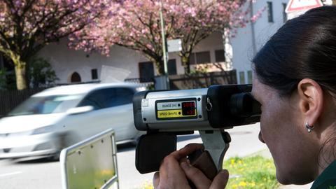 Eine Polizistin kontrolliert mit einem Laser-Messgerät den Verkehr
