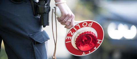 Polizeibeamtin mit einer Verkehrskelle in der Hand