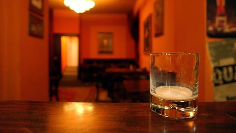 Ein leeres Glas auf einem Tresen in einer leeren Kneipe