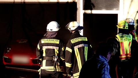 Feuerwehrleute stehen vor einer Garage, in der ein roter Sportwagen parkt.