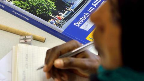 """Eine Frau mit Stift in der Hand, im Hintergrund ein Buch: """"Deutsch im Alltag"""""""
