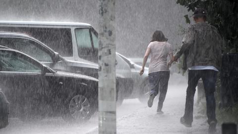 Zwei Männer rennen durch Regen zu ihren Autos.
