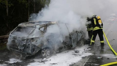 Feuerwehrleute löschen brennendes Auto