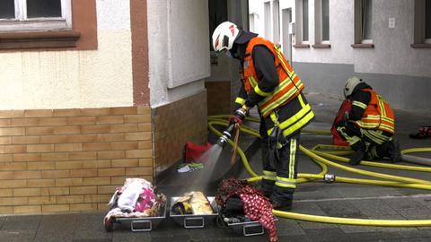 Feuerwehrleute löschen brennende Gegenstände, die vor dem Haus auf dem Boden liegen.