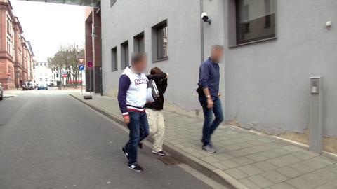 Beamte der Kriminalpolizei führen den Verdächtigen (Mitte) ab.