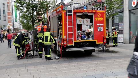 Ein Feuerwehrauto steht auf einer Einkaufsstraße in der Innenstadt.
