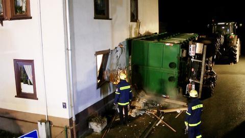 Der Anhänger des Traktors ist durch die Hauswand gebrochen.