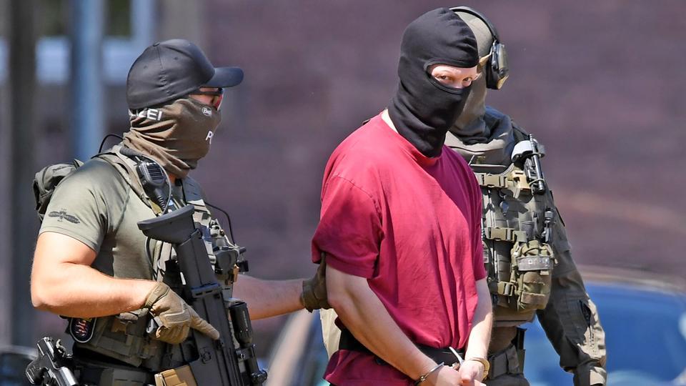 Stephan E. mit Handschellen und Gesichtsmaske scharf bewacht von bewaffneten Polizisten auf dem Weg zu einem Hubschrauber