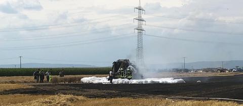 Brennende Strohballenpresse auf einem Feld bei Flörsheim-Wicker