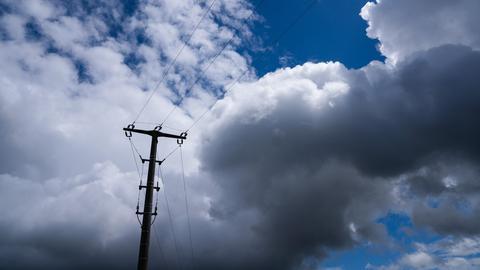 Ein Strommast hebt sich vor dem stark bewölkten Himmel ab.