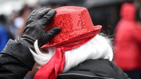 Eine Frau hält ihren Hut bei einem Fastnachts-Umzug.