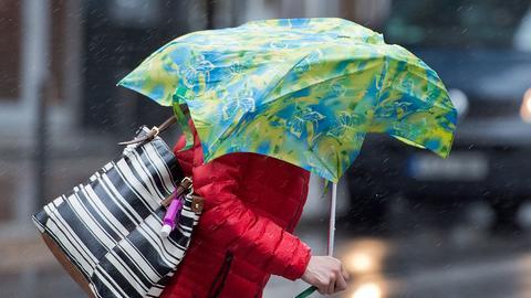 Eine Passantin hält einen vom Wind eingedrückten Regenschirm in der Hand.