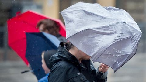 Menschen mit Regenschirm im Wind