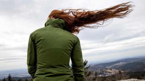 Die roten Haare einer Frau wehen im Wind. Sie steht mit einer grünen Jacke bekleidet mit dem Rücken zu den Bildbetrachtenden.
