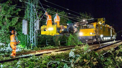 Mitarbeiter der Deutschen Bahn räumen Äste von den Bahngleisen bei Kriftel.