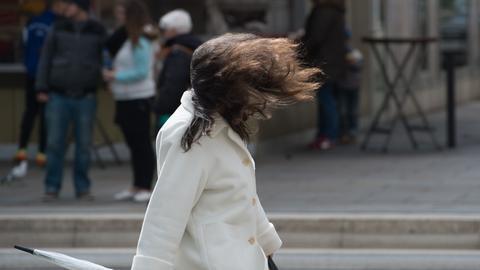 Heftiger Wind wirbelt einer Frau mit Regenschirm in der Hand die Frisur durcheinander