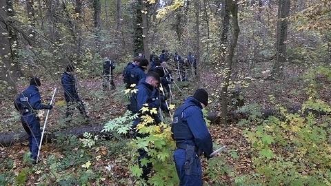 Polizisten durchkämmen einen Wald auf der Suche nach einer Vermissten.