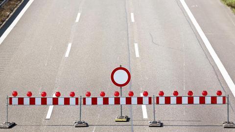 """Eine leere dreispurige Autobahn aus der Vogelperspektive fotografiert. Vorne stehen Absprerrgitter und ein """"Einfahrt verboten-Schild""""."""