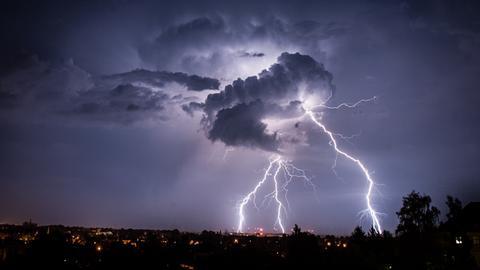 Drei Blitze brechen aus einer Wolke hervor.