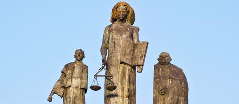 Steinerne Statue der Justitia in der Abendsonne auf einem Dach installiert. Sie wird eingerahmt von zwei weiteren Statuen.