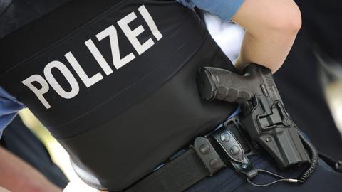 Ein hessischer Polizist in Uniform mit Dienstwaffe