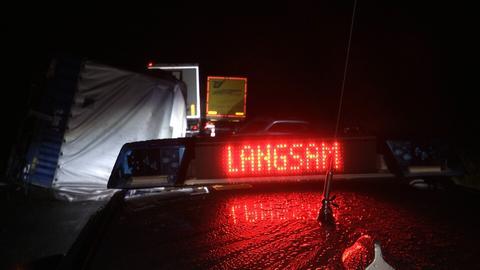"""Leuchtschrift """"Langsam"""" auf einem Polizeiwagen im Einsatz."""