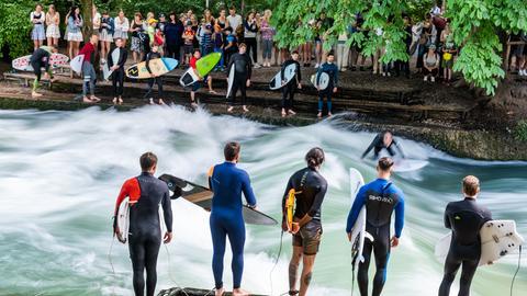 Surfer und Schaulustige auf dem Eisbach in München