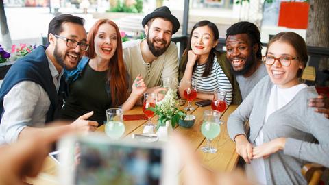 Junge Menschen sitzen draußen bei gutem Wetter eng beieinander und lächeln in eine Handykamera.