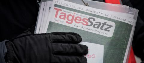 Eine Hand mit Handschuh hält eine Ausgabe des Tagessatzes aus Kassel
