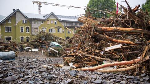 """Holz und Trümmerteile türmen sich in riesigen Bergne im Flussbett der Ahr vor dem zerstörten Hotel mit dem Namen """"Ahrtal"""" im Hintergrund."""