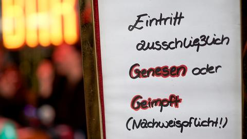 """Ein Papier, auf dem geschrieben steht: """"Eintritt nur Genesen oder Geimpft (Nachweispflicht!)"""" - an einer Glastür."""