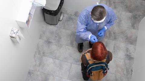 Ein Mitarbeiter eines Testzentrums führt einer Person ein Stäbchen in die Nase. Aus der Vogelperspektive fotografiert.