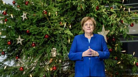 Angela Merkel steht vor einem geschmückten Tannenbaum.