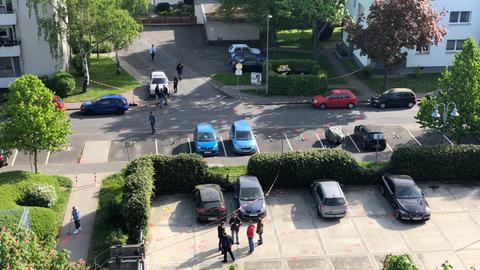 Blick auf den Tatort in Wiesbaden: Auf dem schwarzen Kleinwagen links unten auf dem Parkplatz explodierte der Sprengsatz. Rundherum haben Polizisten Spuren markiert.