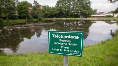 """Schild mit der Aufschrift """"Eltern haften für ihre Kinder"""" an der Teichanlage."""