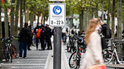 Foto der Frankfurter Fußgängerzone. Im Vordergrund ein Schild mit einem Maskengebot und im Hintergund unscharf Menschen und Polizisten.