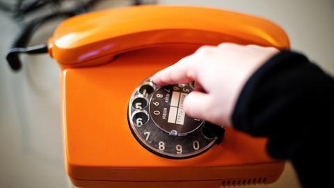 Orangefarbenes Telefon mit Wählscheibe