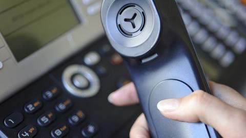 Eine Frauenhand hält einen Telefonhörer eines Festnetztelefon