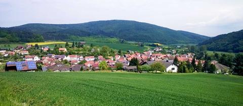 Auf dem Foto ist aus der Ferne der Ort Gellershausen im Landkreis Waldeck-Frankenberg zu sehen - umrandet von Feldern und Bergen.