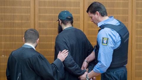 Ein Justizbeamter nimmt dem mutmaßlichen Islamisten im Verhandlungssaal des Landgerichts in Frankfurt die Handschellen ab, während sein Verteidiger Ali Aydin (l) ihm die Hand auf den Arm legt.