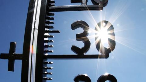 Sonne scheint durch ein Thermometer, das 30 Grad anzeigt
