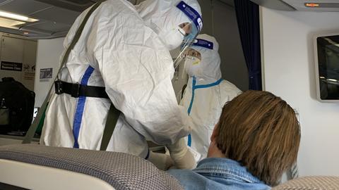 Beamte der chinesischen Gesundheitsbehörden messen bei den Passagieren des Sonderfluges von Frankfurt nach Tianjin die Körpertemperatur.
