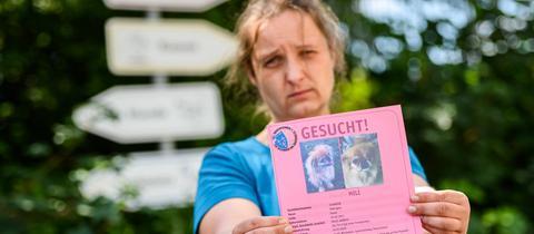 Frau hält Zettel mit gesuchtem Tier in den Händen.