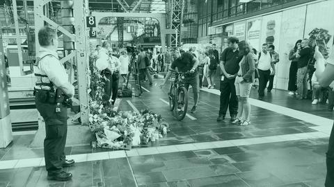 Menschen legen am Gleis am Frankfurter Hauptbahnhof Blumen nieder.