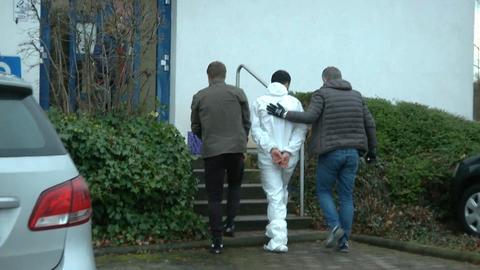 Ein Mann im weißen Schutzanzug und mit Handschellen wird von zwei Männern eine Treppe hinauf begleitet
