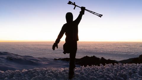 Tom Belz reckt auf dem Gipfel des Kilimandscharo seine Krücken in die Luft