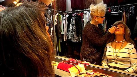 Doris wird von Manuela Mock vor einem großen Spiegel geschminkt.