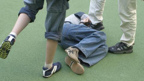 Schüler treten einen auf dem Boden liegenden Jungen.
