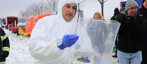 Ein Mann in weißer Schutzkleidung mit medizinischem Gerät